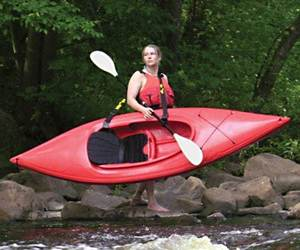 a woman carring a red kayak