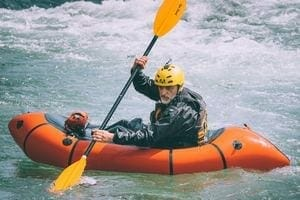 a man in an inflatable kayak in rapids